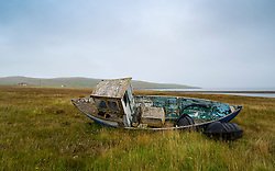 Old fishing boat abandoned in a field at North Roe village, North Roe, Shetland, Scotland, UK