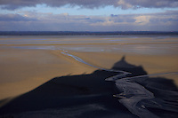 The shadow of Mont San Michel on the surrounding sand off the coast of Normandy, France