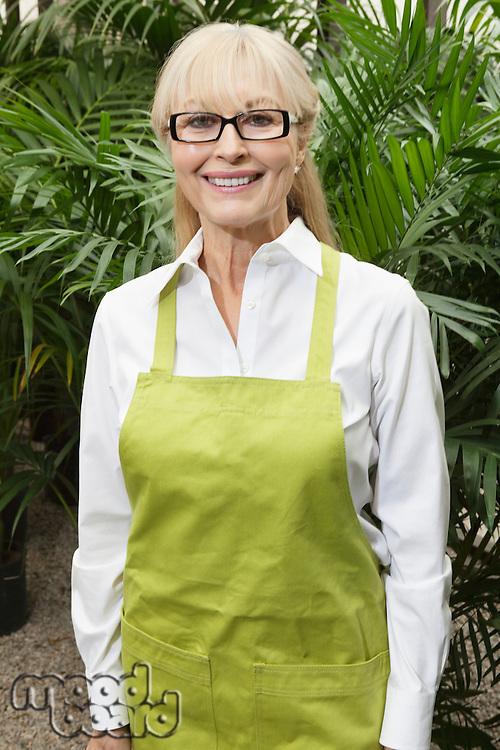 Portrait of a happy senior female gardener with apron standing in botanical garden