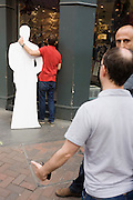 TV man holds a life-size carboard cut-out of Prince William in a London street during filming of vox pop.