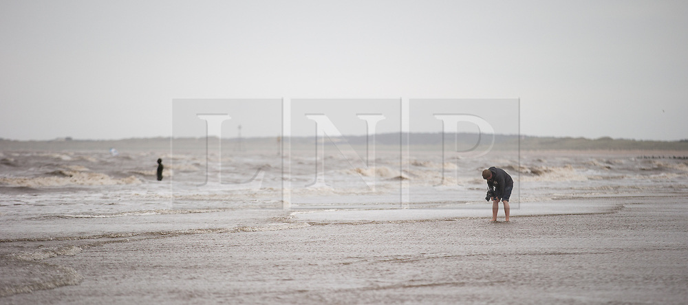 "© Licensed to London News Pictures . Crosby , UK . File picture dated 07/07/2015 of Crosby Beach , featuring a man paddling in the water and an "" iron man "" , a part of Antony Gormley's "" Another Place "" installation . The organisation that brought the installation to the site , Regenerus (or South Sefton Development Trust as it was in Summer 2005) is celebrating the tenth anniversary since its installation , at an exhibition starting today (7th September 2015) at nearby Crosby Lakeside Adventure Centre . Photo credit : Joel Goodman/LNP"