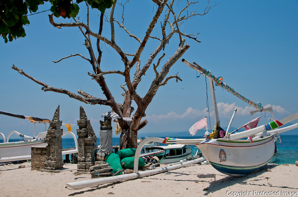 White, sandy beach with boats and a temple on Nusa Penida Islaand, Bali, Indonesia