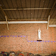 Bloodstained clothes are piled high on the pews under the watch of Virgin Mary, while bloodspatter and bullet and grenade holes still demonstrate the horror of the Nyamata Church massacre