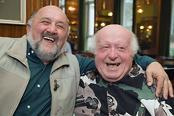Two old friends; smiling,