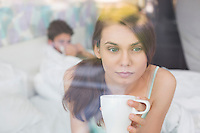 Thougtful woman having coffee at home with man lying in background