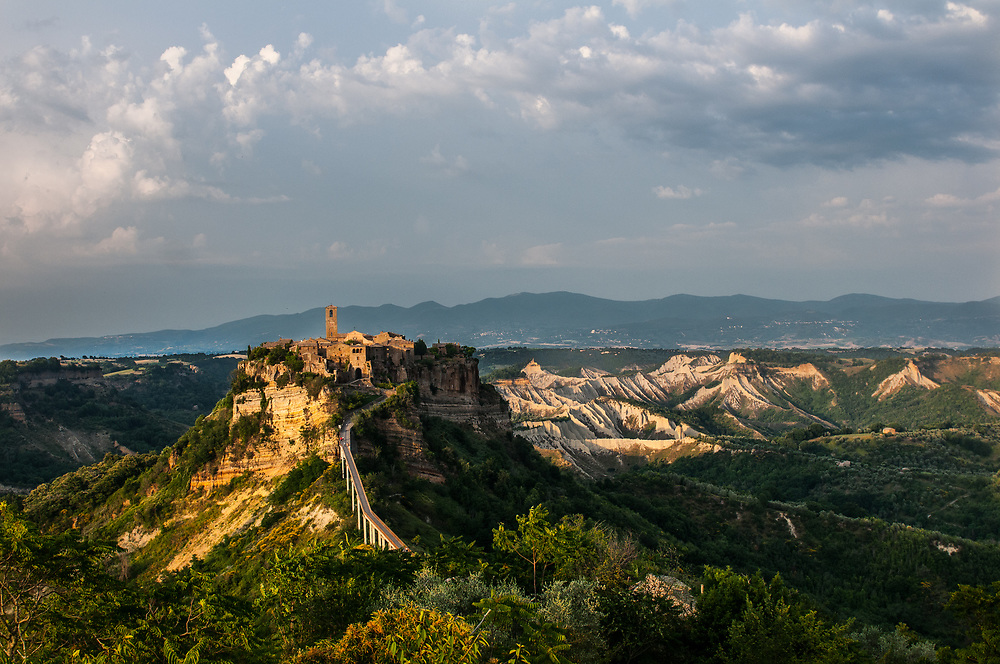 A panoramic view of the village of Civita di Bagnoregio.<br /> Civita di Bagnoregio is a town in the Province of Viterbo in central Italy, a suburb of the comune of Bagnoregio, 1 kilometre (0.6 mi) east from it. It is about 120 kilometres (75 mi) north of Rome. Civita was founded by Etruscans more than 2,500 years ago. Bagnoregio continues as a small but prosperous town, while Civita became known in Italian as La citt&agrave; che muore (&quot;The Dying Town&quot;). Civita has only recently been experiencing a tourist revival. The population today varies from about 7 people in winter to more than 100 in summer.The town was placed on the World Monuments Fund's 2006 Watch List of the 100 Most Endangered Sites, because of threats it faces from erosion and unregulated tourism.