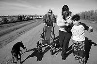 Mary McGinnis, 51, left, and her grandson Alex Acuna,8, right, walk along the levee at in Yuba City with respite worker Gloria Peralta, 26, in preparation for the upcoming protest walk to the state capital in February of 2011. Mary began to organize within the disabled community a march from her home, 40 miles from the state capital, under the name Mommy Tsunami. <br />