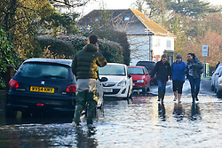 © Licensed to London News Pictures. 12/01/2014. Wraysbury, UK. People walk along a flooded road. Flooding in Wraysbury, Berkshire today 12th January 2014.  Flooding and property damage is expected to continue along the River Thames.  Large areas of Britain are experiencing flooding after wet weather. Photo credit : Stephen Simpson/LNP