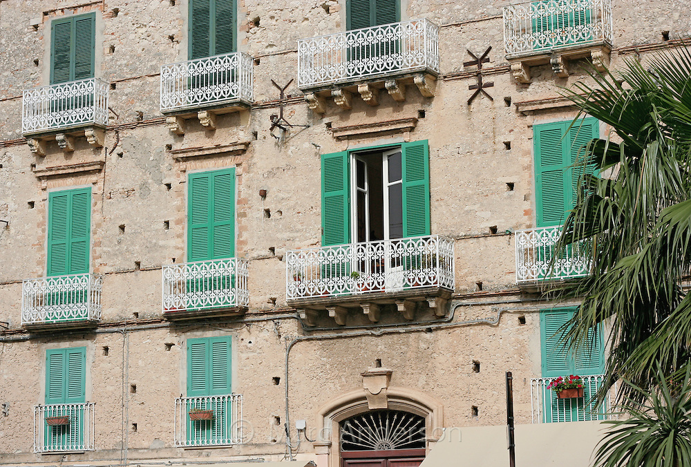 Green shutters and white balconies on an old building in  Tropea, Calabria, Italy