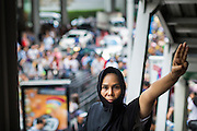 """01 JUNE 2014 - BANGKOK, THAILAND: A woman holds up a three fingered salute during a protest against the Thai military coup at Terminal 21 a popular shopping mall in Bangkok. The salute is from the movie """"The Hunger Games"""" and symbolizes it admiration, thanks and good-bye to a loved one. In this case, the loved one is reportedly Thai democracy. The Thai army seized power in a coup that unseated a democratically elected government on May 22. Since then there have been sporadic protests against the coup. The protests Sunday were the largest in several days and seemed to be spontaneous """"flash mobs"""" that appeared at shopping centers in Bangkok and then broke up when soldiers arrived. Protest against the coup is illegal and the junta has threatened to arrest anyone who protests the coup. There was a massive security operation in Bangkok Sunday that shut down several shopping areas to prevent the protests but protestors went to malls that had no military presence.    PHOTO BY JACK KURTZ"""