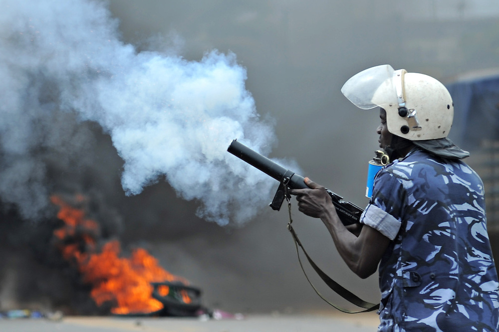 LOME, TOGO - 12-10-05   - A police officer fires tear gas at protesters in the Lomé neighbourhood of Bé. Protesters clashed with police in Lomé on October 5. A peaceful protest was scheduled by opposition groups, but their route was blocked by police.  For months, opposition parties have been calling for the departure of president Faure Gnassingbe, whose family has been in power for over 40 years.   Photo by Daniel Hayduk