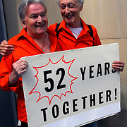 """Gay couple with sign """"52 Years Together"""" at the Gay Pride Parade in New York City"""