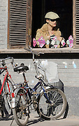 A fashionable woman is seem in a restaurant window in central Beijing's Nanluoguoxiang, a street popular for shopping and dining.