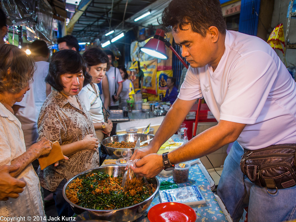 27 SEPTEMBER 2014 - BANGKOK, THAILAND: A vendor sells vegetarian entres during the celebration of the Vegetarian Festival near the Chow Su Kong Shrine in Talat Noi, a Chinese enclave in Bangkok. The Vegetarian Festival is celebrated throughout Thailand. It is the Thai version of the The Nine Emperor Gods Festival, a nine-day Taoist celebration beginning on the eve of 9th lunar month of the Chinese calendar. During a period of nine days, those who are participating in the festival dress all in white and abstain from eating meat, poultry, seafood, and dairy products. Vendors and proprietors of restaurants indicate that vegetarian food is for sale by putting a yellow flag out with Thai characters for meatless written on it in red.    PHOTO BY JACK KURTZ