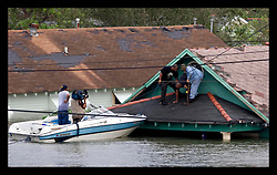 29th August, 2005. Hurricane Katrina hits New Orleans, Louisiana. A man is rescued from the lower 9th ward after it disappeared under water.