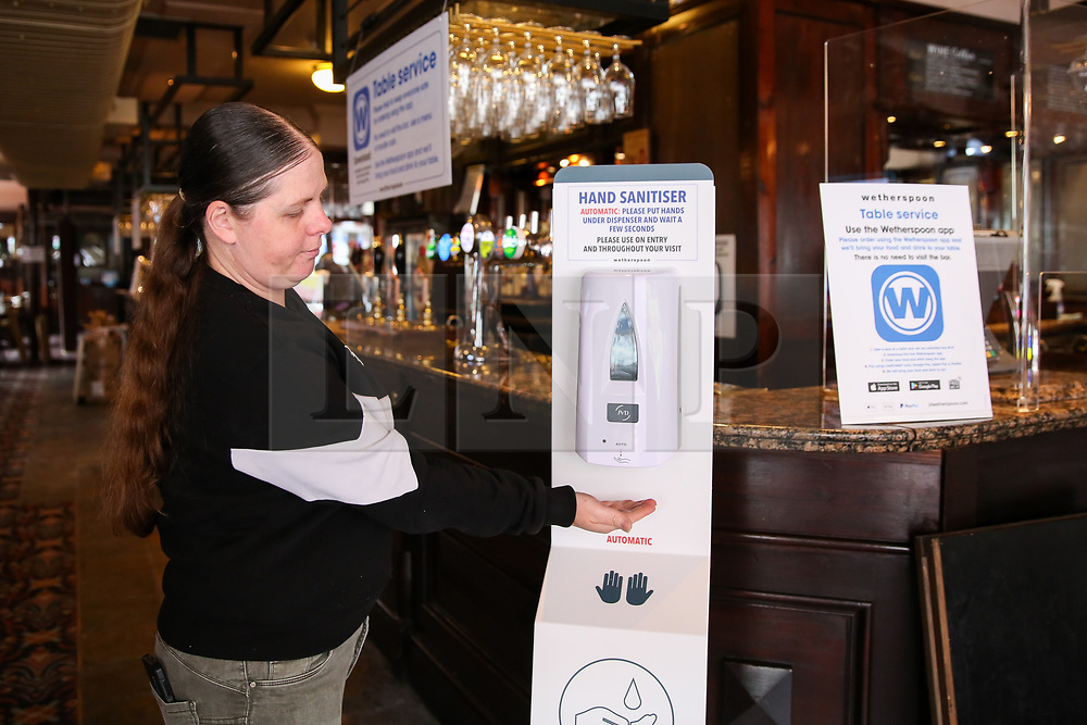 © Licensed to London News Pictures. 03/07/2020. London, UK. A member of staff uses the hand sanitiser left at the entrance to The Toll Gate, a Wetherspoon pub in north London as the pub prepares to reopen on 4 July, the 'Super Saturday'. Pubs across the UK closed on 23 March following the coronavirus lockdown. As COVID-19 lockdown restrictions are eased, pubs will reopen on Saturday 4 July. Some pubs are planning to reopen from 6am. Photo credit: Dinendra Haria/LNP
