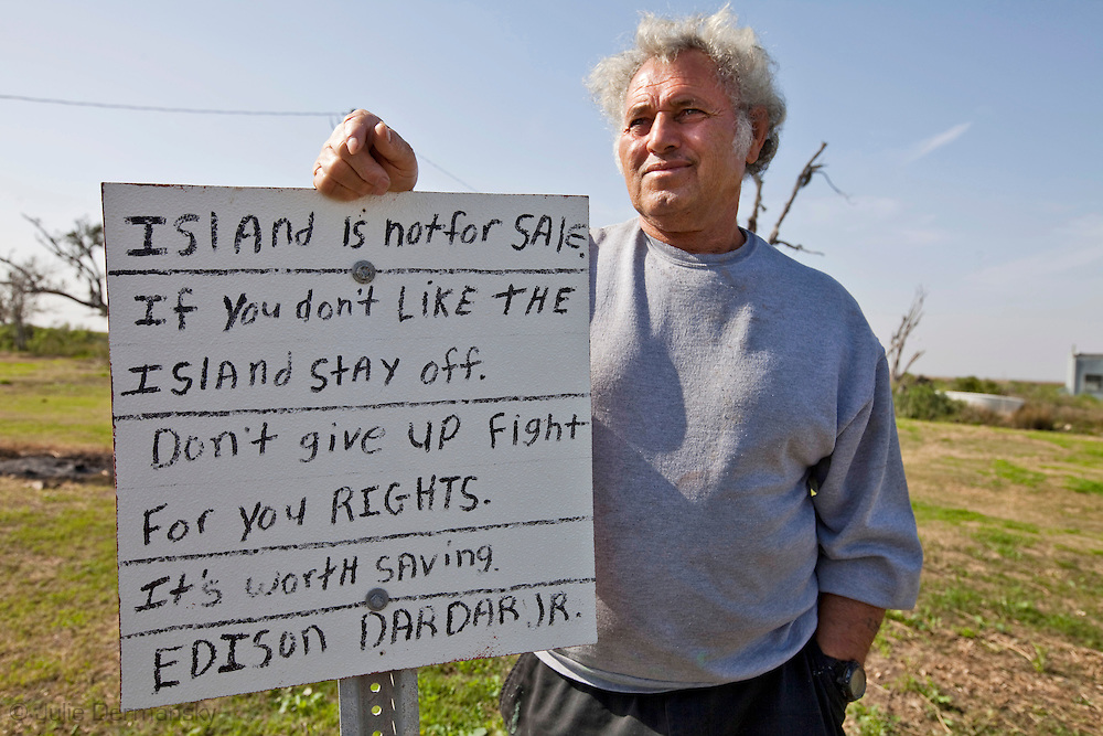 Edison Darder a life long resident of the Isle de Jean Charles standing by a sign his son made. Dardar says he wont leave the Isle de Jean Charles no matter what. Isle de Jean Charles is eroding at a quick pace and will likely be uninhabitable soon.