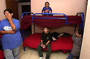 Alvina Villa Zarco, 25, (left), reacts after locating her two sons at Albergue Menor Repatriado, a shelter in Nogales, Sonora, Mexico, for children deported from the U.S. after they entered the country illegally.  Villa Zarco's son, Arturo, 5, (right), watches his mother, along with two other young relatives also smuggled into Nogales, Arizona, USA.