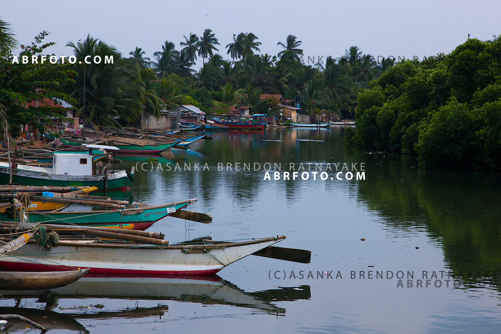 A row of fishermens boat on a tropical lagoon in Negombo.Negombo is a major city in Sri Lanka, located on the west coast of the island and at the mouth of the Negombo Lagoon
