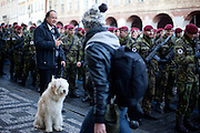 Smoking dog owner talking to Soldiers waiting to attend the mourning procession for former Czech President Vaclav Havel at Prague Castle.