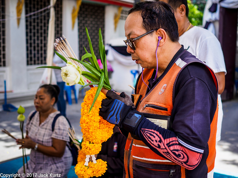 "11 APRIL 2017 - BANGKOK, THAILAND: A motorcycle taxi driver prays at Wat Chana Songkhram in Bangkok during a Songkran merit making service. Songkran is the traditional Thai Lunar New Year. It is celebrated, under different names, in Thailand, Myanmar, Laos, Cambodia and some parts of Vietnam and China. In most places the holiday is marked by water throwing and water fights and it is sometimes called the ""water festival."" This year's Songkran celebration in Thailand will be more subdued than usual because Thais are still mourning the October 2016 death of their revered Late King, Bhumibol Adulyadej. Songkran is officially a three day holiday, April 13-15, but is frequently celebrated for a full week. Thais start traveling back to their home provinces over the weekend; busses and trains going out of town have been packed.     PHOTO BY JACK KURTZ"