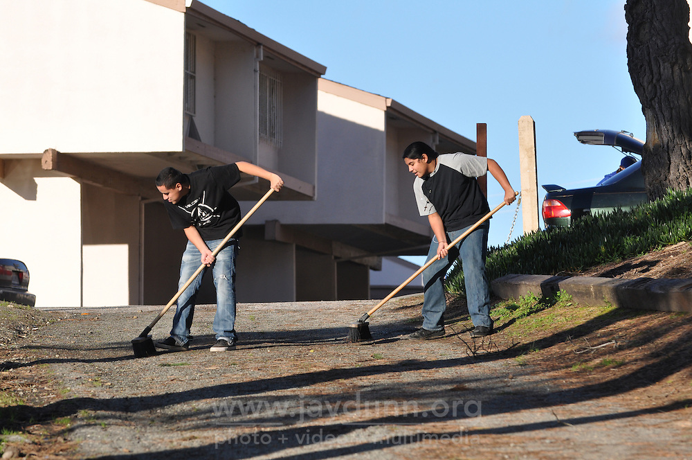 Youth volunteer to sweep the access road during a community cleanup on Tuesday, February 2nd, 2016 at the nearly-completed Acosta Plaza Recreation Area in east Salinas, CA.