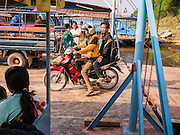 11 MARCH 2013 - ALONG HIGHWAY 13, LAOS: A motorcyclist boards a Mekong River ferry for the short ride to Luang Prabang. The Mekong River ferries are disappearing as bridges across the river are completed and roads along the river are paved. The paving of Highway 13 from Vientiane to near the Chinese border has changed the way of life in rural Laos. Villagers near Luang Prabang used to have to take unreliable boats that took three hours round trip to get from the homes to the tourist center of Luang Prabang, now they take a 40 minute round trip bus ride. North of Luang Prabang, paving the highway has been an opportunity for China to use Laos as a transshipping point. Chinese merchandise now goes through Laos to Thailand where it's put on Thai trains and taken to the deep water port east of Bangkok. The Chinese have also expanded their economic empire into Laos. Chinese hotels and businesses are common in northern Laos and in some cities, like Oudomxay, are now up to 40% percent. As the roads are paved, more people move away from their traditional homes in the mountains of Laos and crowd the side of the road living off tourists' and truck drivers.    PHOTO BY JACK KURTZ