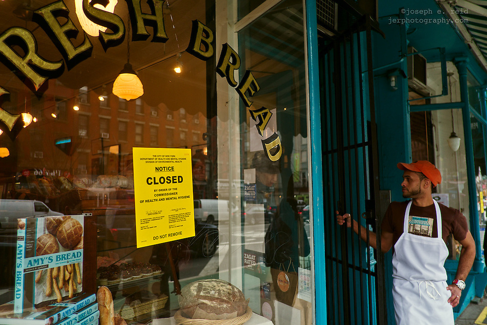 Worker at door of bread shop just ordered closed by health department, New York, NY, US