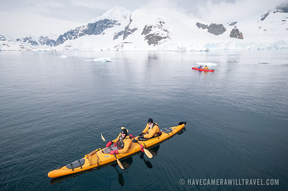 Kayakers in tandem kayaks in calm waters  at Cuverville Island on the Antarctic Peninsula. View from above.