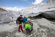 Alfredo Hoch (green jacket) and his wife Anja Behrens get ready to trek on the Rohone Glacier along with their friend Ronny Miestas.  <br /> Huge sheets with fleece blankets that cover an ice tunnel at the mouth of the Rhone Glacier in Switzerland. After a winter with record amounts of snow, most of it was gone when this imae was taken on July 14th 2018, exposing the darker ice. While snow is a brilliant reflector of the energy from the sun, the darker ice absorbs the energy instead, accelerating the melting of the glacier. The color and darkness of glacier ice vary all over the world, depending on build-up of pollution, age of the ice, particles picked up by the ice and by microorganisms in the ice. The glacier ice is however rarely white as snow. With shorter winters and vanishing snow cover, the melting of the glaciers is accelerating.<br /> The Rhone Glacier now melts more than 70 centimeters in thickness every week during the summer months. Between 1996 and 2006, an estimated 0.9 billion cubic metres of water melted yearly from the Swiss glaciers. That number is likely much higher today. Switzerland just had the hottest July since 1921, and the rivers are running at record low levels.<br /> The ice tunnel is a popular tourist attraction, and has been a steady income source for the Carlen family who runs and maintain the ice tunnel. The fleece blankets help slow down the melting. While tourists always have flocked to the Rhone Glacier due to it's easy access from the nearby Furka Pass, today's tourism is often visitors who are concerned about the effects of climate change.