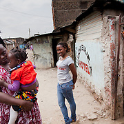 Caroline Mbulwa, 24, outside her house with her mother and siblings. Caroline is a Nairobits graduate and now works a successful web designer. She is the sole provider of the family and with her income they have managed to buy a new home in a better part of the slums.  Nairobits is a charity teaching kids from Nairobi's slums It and train them to get work in the IT sector.Every year 1mill young people graduate and leave school and only 1/3 have any hope of getting a job. Nairobits aim to train more than 500 young people / year from the slums, some with only basic formal education, how to set up their own business or get a job in the growing IT sector in Kenya.