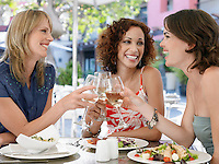 Three female friends toasting drinks at outdoor cafe