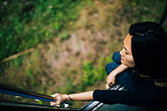 A young Asian woman rides a train in hill country, Ella, Sri Lanka, Asia