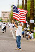 10 APRIL 2006 - PHOENIX, AZ: A man carries an American flag through Phoenix, near the Arizona state capitol Monday. More than 200,000 people participated in a march for immigrants's rights in Phoenix Monday. The march was a part of a national day of action on behalf of undocumented immigrants. There were more than 100 such demonstrations across the US Monday. Protestors were encouraged to wear white, to symbolize peace, and wave American flags, to demonstrate their patriotism to the US.  Photo by Jack Kurtz