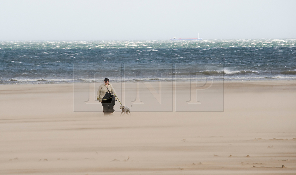 © Licensed to London News Pictures. 12/09/2011..Saltburn Beach, Saltburn, Cleveland, England...A woman walks through blowing sand as strong winds blow across the beach at Saltburn in Cleveland...Photo credit : Ian Forsyth/LNP