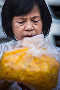 26 JANUARY 2013 - BANGKOK, THAILAND:   A woman prays with a handful of marigolds before laying them in the path of monks making a pilgrimage in Bangkok. 1,128 Buddhist monks from the Dhammakaya movement took part in a 25-day pilgrimage walk passing through Bangkok and several provinces in central Thailand, as part of a voluntarily undertaking of ascetic practices. The pilgrimage is scheduled to end Sunday, January 27 at Wat Phra Dhammakaya near Bangkok. Along the way Thai Buddhists laid marigolds along their path and greeted them for merit making. The Dhammakaya is the fastest growing Buddhist movement in Thailand. The pilgrimage is reported to be the largest pilgrimage in Thailand and organizers hope to get it placed in the Guiness World Records book.    PHOTO BY JACK KURTZ