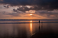 Two figures looking into the sunset under dark clouds at Seminyak Beach in Bali, Indonesia