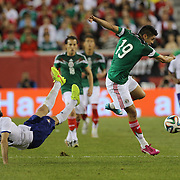 Oribe Peralta, (right), Mexico, evades the challenge of Luis Neto, Portugal, during the Portugal V Mexico International Friendly match in preparation for the 2014 FIFA World Cup in Brazil. Gillette Stadium, Boston (Foxborough), Massachusetts, USA. 6th June 2014. Photo Tim Clayton