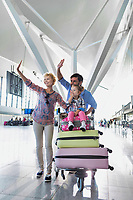 Portrait of happy family waving in arrival area at airport