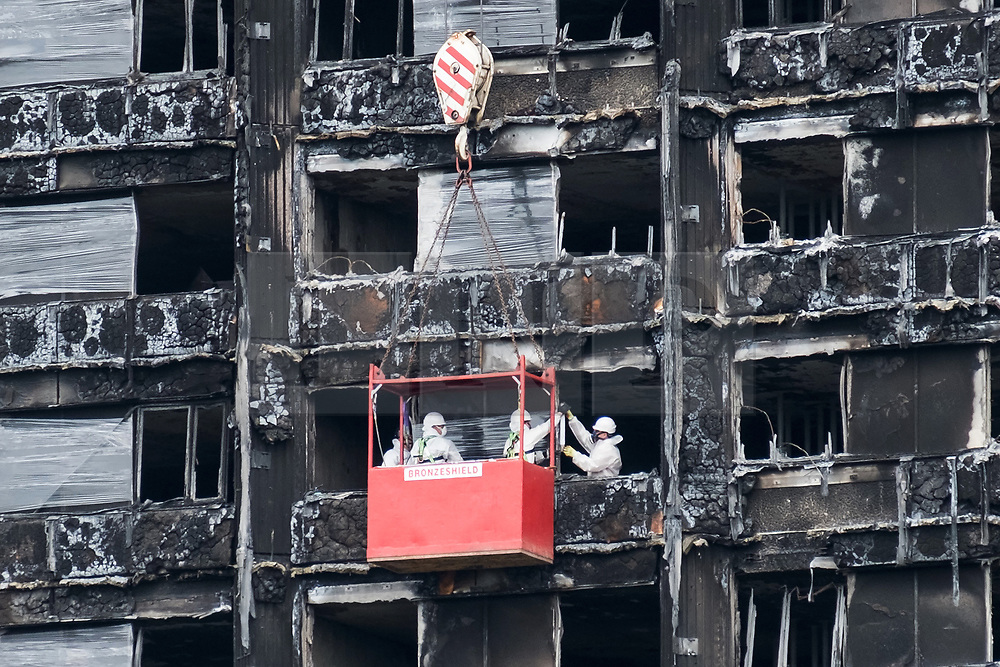 © Licensed to London News Pictures. 16/08/2017. London, UK. Workmen in a crane outside the Grenfell residential tower block in West London are seen wrapping the tower with a cling film type material. The tower was engulfed by a fire two months ago causing at least 80 deaths and over 70 injuries. Up to 200 survivors are still living in hotels and have resorted to searching for new homes themselves out of frustration at the council's rehousing efforts. Photo credit: Ray Tang/LNP