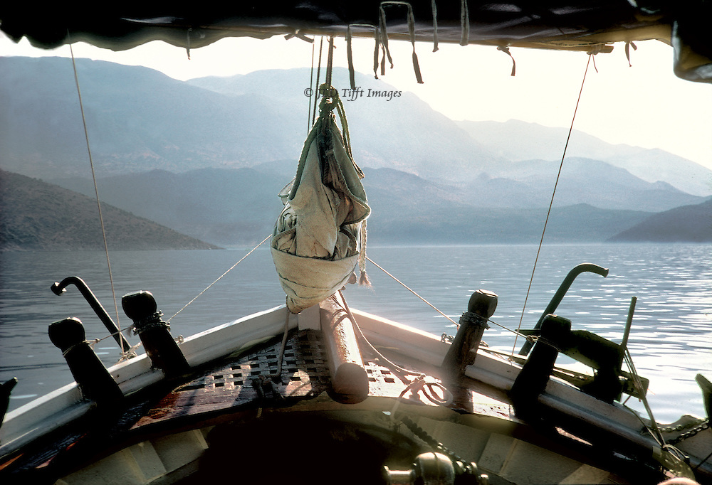 View of the coast of Lycia, Turkey, from the prow of a wooden gulet; passenger's viewpoint.  Folded spinnaker on the bowsprit makes a teardrop shape.  Beyond, hills and mountains fading away.