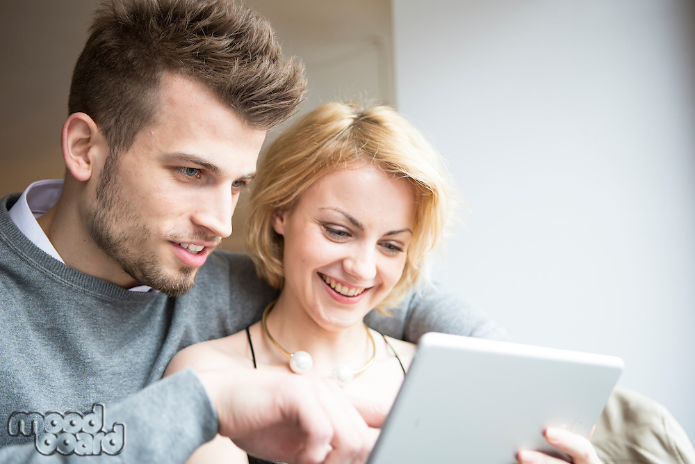 Happy young couple using digital tablet in cafe