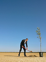 Businessman planting tree in desert full length
