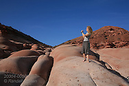 Woman takes photo standing on red sandstone cliffs of Puerto Gato, Baja, Mexico.