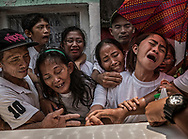 "Family members of Junmar Abletes, killed in an extrajudicial killing by black-masked assassins in President Duterte's so-called ""War on Drugs"", resist an attempt to close his coffin at Navotas Cemetery in Metro Manila.  Junmar's father, Pedro, on far left, supports mother, Lucia, as siblings mourn in their final moments before his body is interred into its tomb chamber.  Family members insist that Junmar was no longer a drug user but was targeted, as his name was apparently on a hit list, while he had returned from the island of Samar to gather up his parents and return with them so that they could visit him in his adopted home there.  Navotas, Philippines."