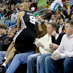 January 22, 2011; New Orleans, LA, USA; San Antonio Spurs point guard Tony Parker (9) crashes into fans sitting courtside while attempting to save a loose ball from going out of bounds during the first quarter against the New Orleans Hornets at the New Orleans Arena.   Mandatory Credit: Derick E. Hingle