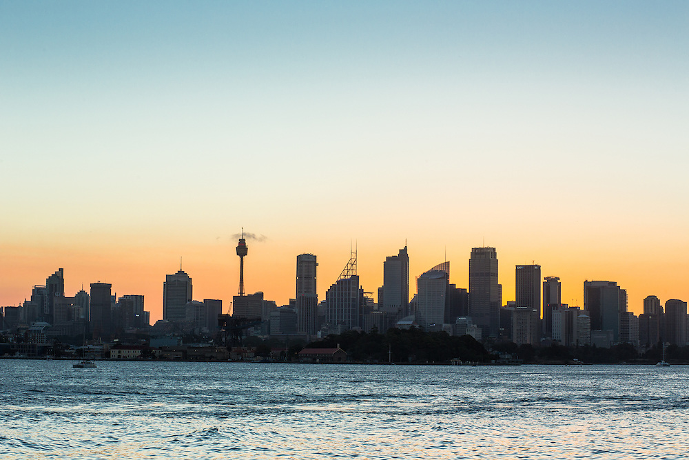 The sillhouette of Sydney city at sunset from Bradleys Head Amphitheatre.