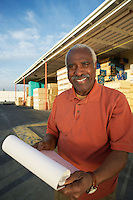 Manager with Paperwork by Loading Dock of Lumber Warehouse