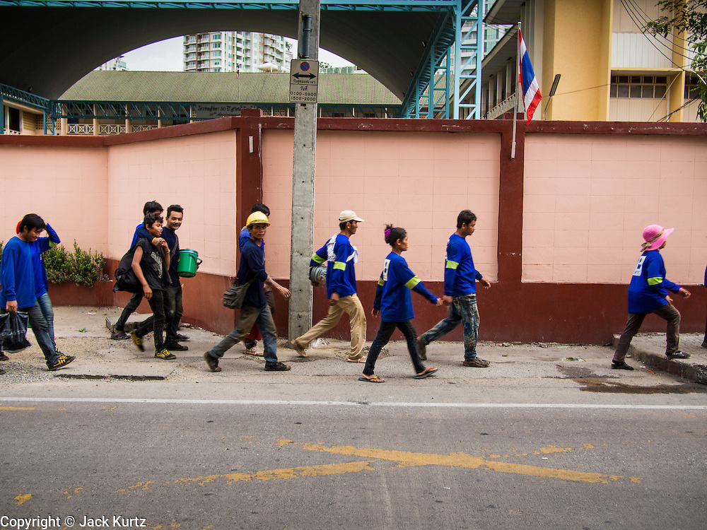 """20 AUGUST 2013 - BANGKOK, THAILAND:  Thai construction workers walk home after a day on the job in Bangkok. Thailand entered a """"technical"""" recession this month after the economy shrank by 0.3% in the second quarter of the year. The 0.3% contraction in gross domestic product between April and June followed a previous fall of 1.7% during the first quarter of 2013. The contraction is being blamed on a drop in demand for exports, a drop in domestic demand and a loss of consumer confidence. At the same time, the value of the Thai Baht against the US Dollar has dropped significantly, from a high of about 28Baht to $1 in April to 32THB to 1USD in August.    PHOTO BY JACK KURTZ"""