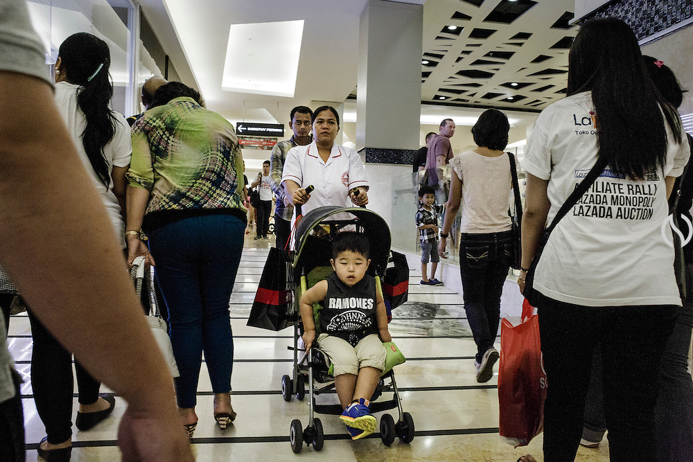 JAKARTA - INDONESIA; SUNDAY, SEPTEMBER 7, 2014; INDONESIA ECONOMIC RISING: An Indonesian housemate push a boy in a push cart while having recreation at Kota Kasablanka Mall in Business District of Jakarta, Indonesia, Sunday, September 7, 2014. According to Asian Development Bank's 2014 report, Indonesia economy growth potential is in creative industry after for years relies heavily on natural resources such as mineral mining and palm oil. By the presidency of Joko Widodo, as a product of the third people election after the People Power Revolution in 1998, Indonesia is more confident in the economy growth and optimistic to become equal in quality to Brazil and China's economy growth. The emerging of Indonesia economy for the last one and a half decade after the end of Suharto's Dictatorship has been in significant way, the per capita growth has reached 400% under Susilo Bambang Yudhoyono presidency. Indonesia is home for 74 million of middle class as estimated by Boston Consulting Group, and  will double in 2020.
